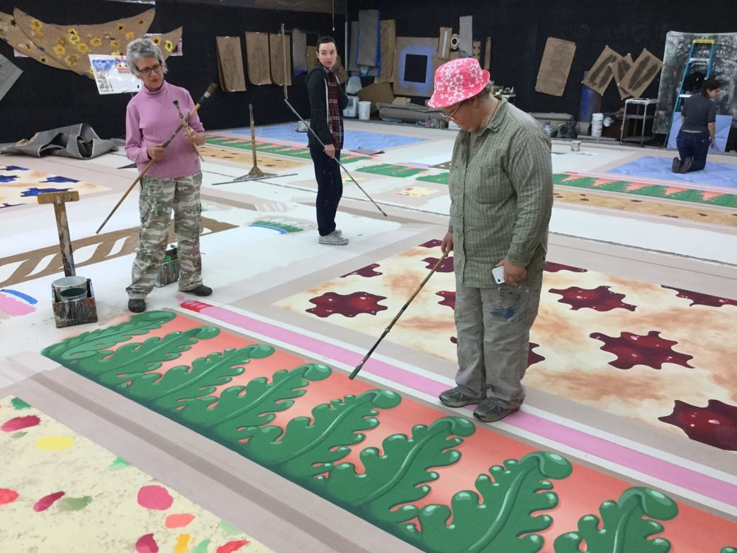 Color-coordinated scenic artists Rachel Keebler and Kim Williamson tackle the Acanthus Leaves as Jessica Carpenter looks on.